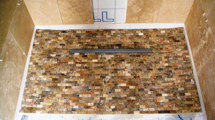 CSmall mosaics laid in shower area to align with linear drain channel after Shower Drain Unclogging
