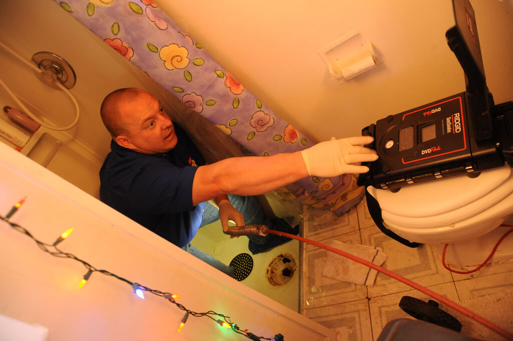 Man Using a Rigid SeeSnake in the field and checking out the shower drain with a lighted camera for Shower Drain Unclogging