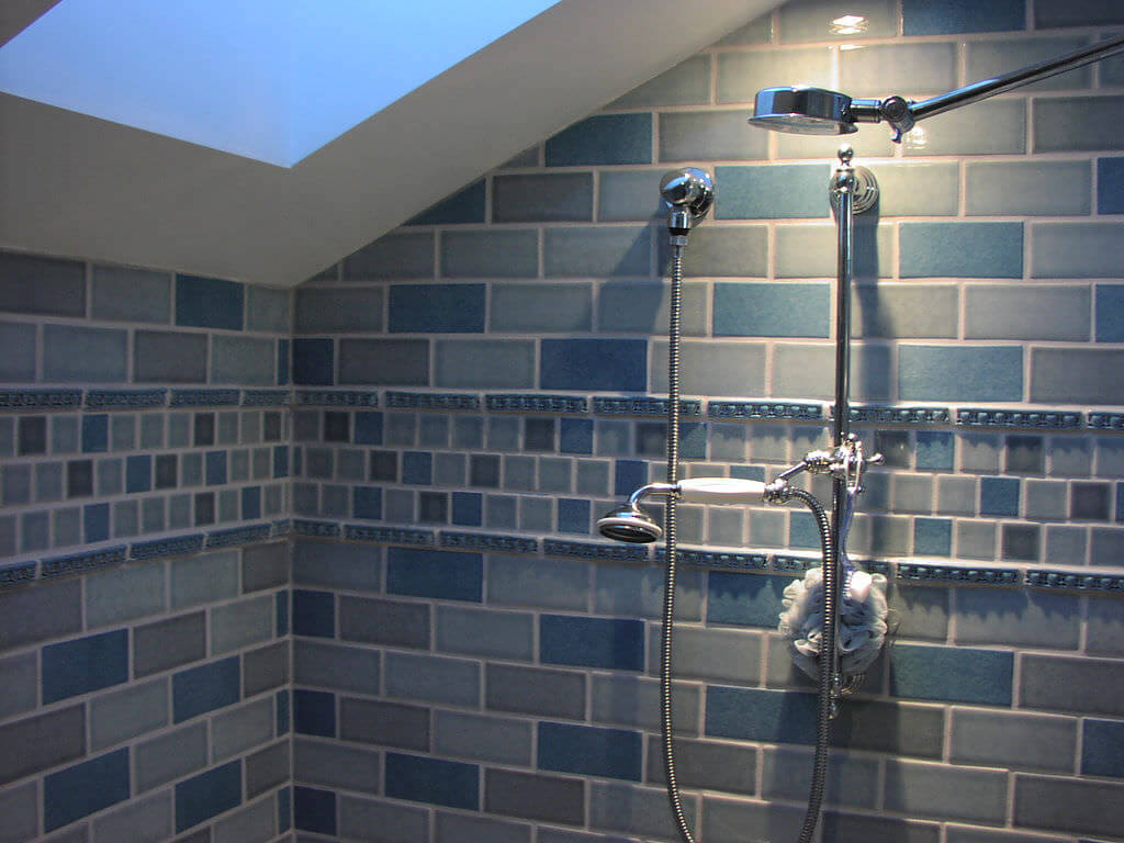newly remodeled bathroom with dual shower heads and blue subway tile after successful Showerhead Installation