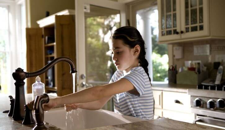 A girl washes her hand in a sink powered by one of the best well pressure tanks