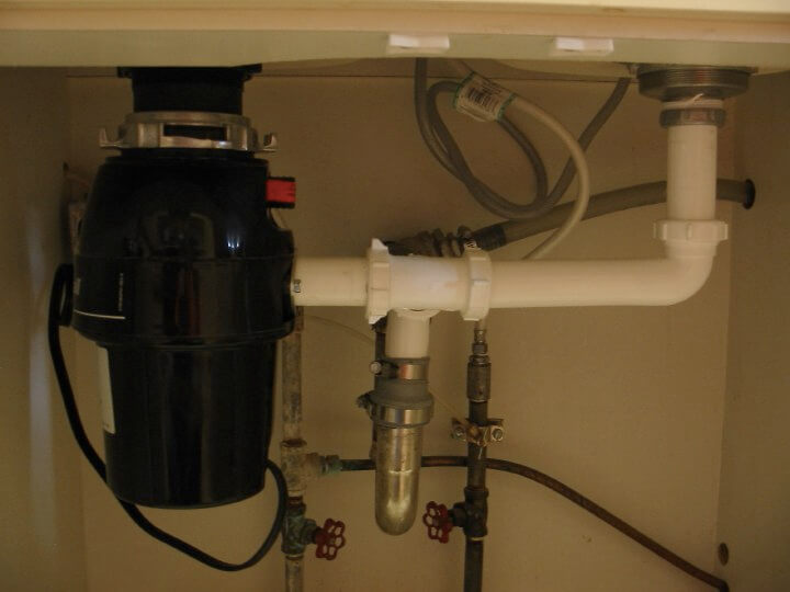 Kitchen drain plumbing with garbage disposal unit installed.
