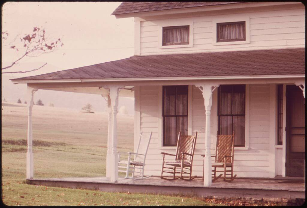 Plumbing problems: Old farmhouse with rocking chairs on the porch
