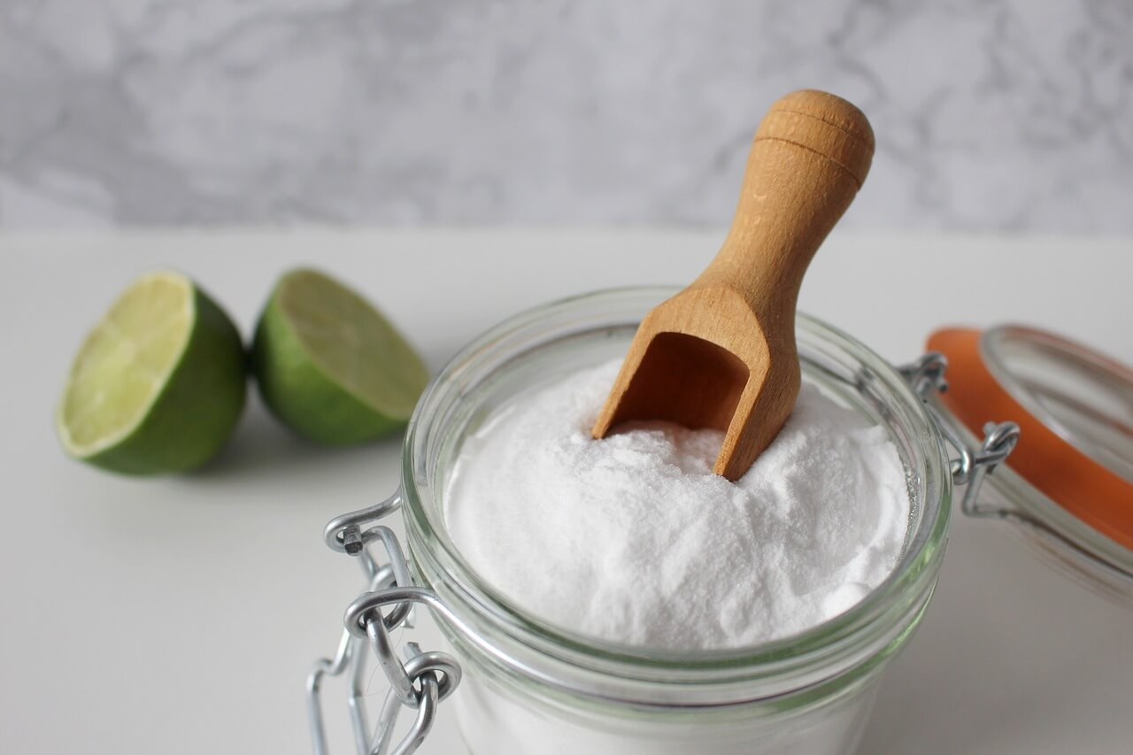 Baking soda in a jar and sliced Lime fruit